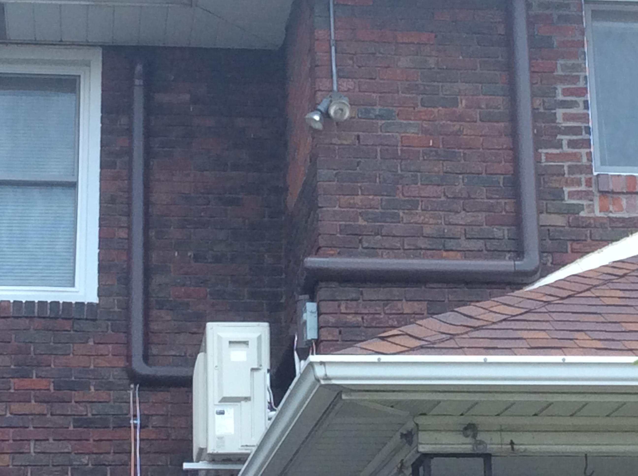 An air conditioning system installed outside of a brick home for the top floor of a duplex in Pittsburgh, Pennsylvania.