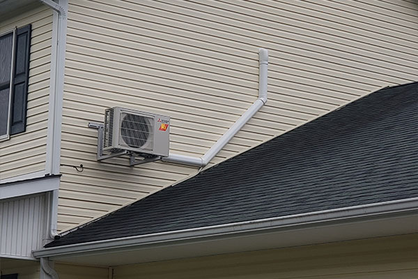 An outdoor air conditioning unit installed on the second floor of a sided house in Pittsburgh, PA.
