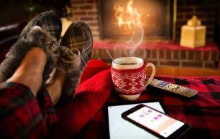 Woman's feet in cozy fur and plaid slippers rests in front of a fireplace with her cup of coffee and iPhone.