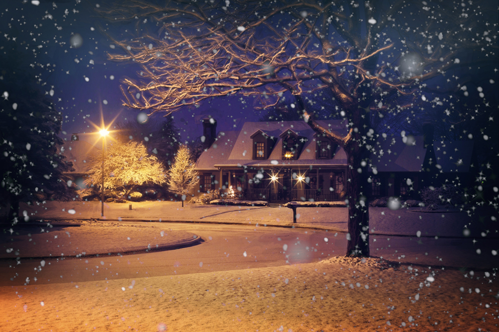 A beautiful house positioned at the end of a cul-de-sac is gathering snow during a night time storm.