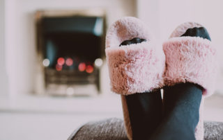 A woman's feet with pink fuzzy slippers are propped up on an ottoman in front of a fire place