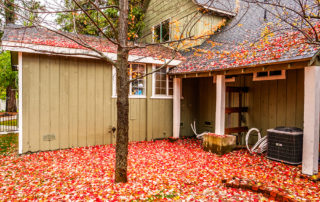 A home in Pittsburgh, PA gathers leaves as the air conditioning unit sits out exposed to the Fall time elements. Should you purchase a new furnace or schedule furnace repair?